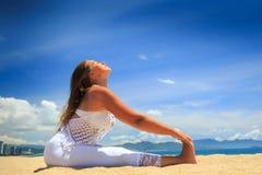 Mädchen in der Spitze in Yoga asana Rumpfbeugen auf Strand gegen Himmel Stockbild