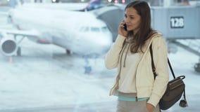 Mädchen in der Sportkleidung und mit dem Rucksack, der am Fenster im Flughafen steht und auf Telefonhintergrund des Flugzeugs spr stock video