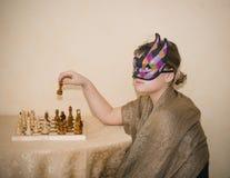 Mädchen in der Theatermaske, die hinter der Tabelle sitzt und Schach spielt Stockfoto