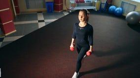 Mädchen in der Turnhalle, die Laufleinen mit Dummköpfen tut Übung auf den Muskeln des Schenkels und der Hinterteile stock video