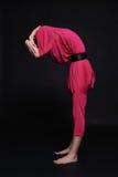 Mädchen in der ungewöhnlichen Kleidung und in der merkwürdigen Haltung Stockfotografie