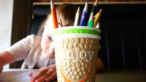 Mädchen an der verfassenden Zeichnung der Tabelle färbte Bleistifte vektor abbildung
