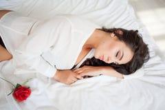 Mädchen in der Wäsche, die auf einem Bett mit einer Rose liegt Lizenzfreie Stockfotografie