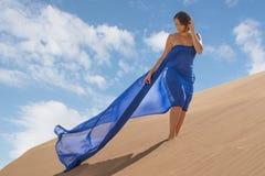 Mädchen in der Wüste mit blauer flüssiger Seide Lizenzfreie Stockfotografie