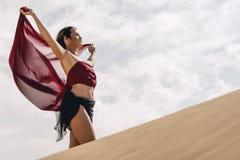Mädchen in der Wüste mit roter flüssiger Seide Stockbild