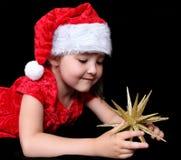 Mädchen in der Weihnachtsausstattung, die mit goldenem Stern spielt Lizenzfreies Stockfoto