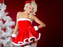 Mädchen in der Weihnachtsmann-Klage über rotem Hintergrund Stockbilder
