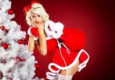 Mädchen in der Weihnachtsmann-Klage über rotem Hintergrund Lizenzfreie Stockfotos