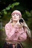 Mädchen in der Weinlesekleidung tut Make-up lizenzfreies stockbild