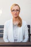 Mädchen des blonden Haares, das auf der Bank in der eleganten Klage sitzt Lizenzfreies Stockfoto