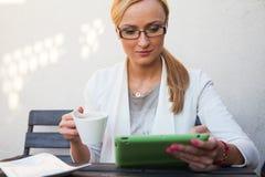 Mädchen des blonden Haares, das hinter der Tabelle mit Tasse Kaffee sitzt und Stockfotografie