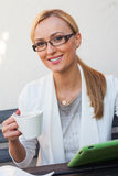 Mädchen des blonden Haares, das hinter der Tabelle mit Tasse Kaffee sitzt und Lizenzfreies Stockfoto