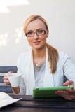 Mädchen des blonden Haares, das hinter der Tabelle mit Tasse Kaffee sitzt und Stockfotos