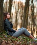 Mädchen des jungen jugendlich in blühendem Frühlingswald auf Hintergrund von Bäumen und von Sonnenuntergang lizenzfreie stockfotografie