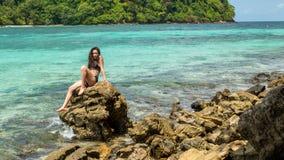 Mädchen des jungen jugendlich im schwarzen Badeanzug, der auf Felsen sitzt stockfotos