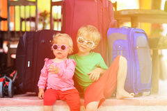 Mädchen des kleinen Jungen und des Kleinkindes, das auf Koffern sitzt Stockfotos