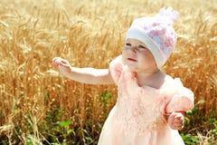 Mädchen des kleinen Kindes, das auf dem Weizengebiet sich wundert Lizenzfreie Stockbilder