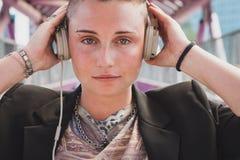 Mädchen des recht kurzen Haares, das Musik auf einer Brücke hört Lizenzfreie Stockbilder