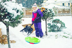 Mädchen des schulpflichtigen Alters, das mit Schaufel im schneebedeckten Yard des Winters arbeitet Lizenzfreies Stockfoto