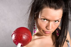 Mädchen des schwarzen Haares mit großem Erdbeerebonbon stockfotos