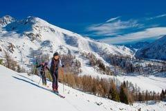 Mädchen des Skibergsteigens zwei aufwärts in Richtung zu einem Berg stockfoto