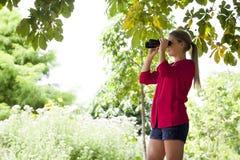 Mädchen des Sommers 20s mit Ferngläsern, ihre Umwelt beobachtend Stockbild