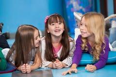 Mädchen, die auf Boden im Kindergarten liegen lizenzfreies stockbild