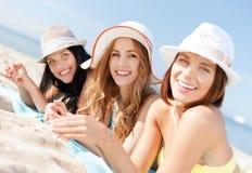 Mädchen, die auf dem Strand ein Sonnenbad nehmen Stockfotos