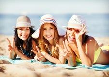 Mädchen, die auf dem Strand ein Sonnenbad nehmen Lizenzfreie Stockfotos