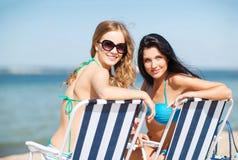 Mädchen, die auf den Strandstühlen ein Sonnenbad nehmen Stockfotos