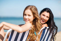 Mädchen, die auf den Strandstühlen ein Sonnenbad nehmen Stockfoto