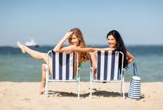 Mädchen, die auf den Strandstühlen ein Sonnenbad nehmen Lizenzfreie Stockfotografie