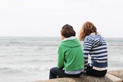 Mädchen, die auf der Wand betrachtet Meer sitzen stockfoto