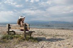 Mädchen, die auf einer Bank betrachtet das Meer sitzen Lizenzfreies Stockfoto