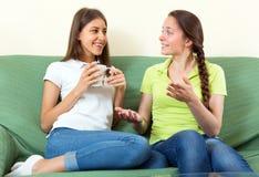 Mädchen, die auf einer Couch sprechen Stockfotos