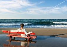 Mädchen, die auf einer roten Bank auf dem Strand sitzen stockfoto