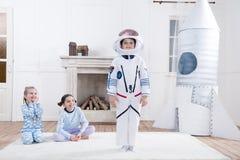 Mädchen, die auf Jungen im Astronautenkostüm schauen stockbilder