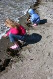 Mädchen, die auf sandigem Strand spielen stockfotos