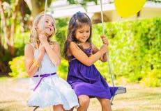 Mädchen, die auf Schwingen spielen Lizenzfreies Stockbild