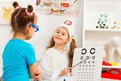 Mädchen, die Augenarzt und Patienten am medizinischen Raum spielen Lizenzfreies Stockfoto
