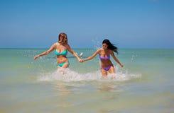 Mädchen, die aus Wasser heraus laufen Lizenzfreies Stockfoto