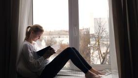 Mädchen die Blondine liest das Buch stock video