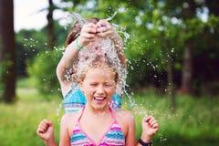 Mädchen, die den Spaß im Freien mit Wasserballonen haben Stockbild