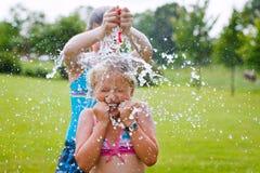 Mädchen, die den Spaß im Freien mit Wasserballonen haben Lizenzfreie Stockfotos