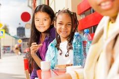 Mädchen, die draußen auf roten Bänke im Café sitzen Lizenzfreie Stockfotografie