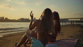 Mädchen, die ein Getränk auf Ozeansonnenuntergang sich entspannen und genießen stock footage