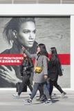 Mädchen, die in Einkaufsviertel mit Modeanschlagtafeln, Peking, China gehen Lizenzfreie Stockfotografie