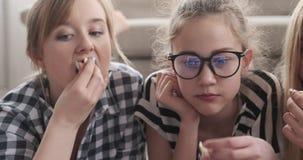 Mädchen, die Film aufpassen und Popcorn essen stock footage