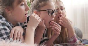 Mädchen, die Film beim Essen des Popcorns aufpassen stock footage