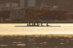 Mädchen, die goldenen Sonnenuntergang Team Passing Cargo Containers Durings rudern stockfotografie